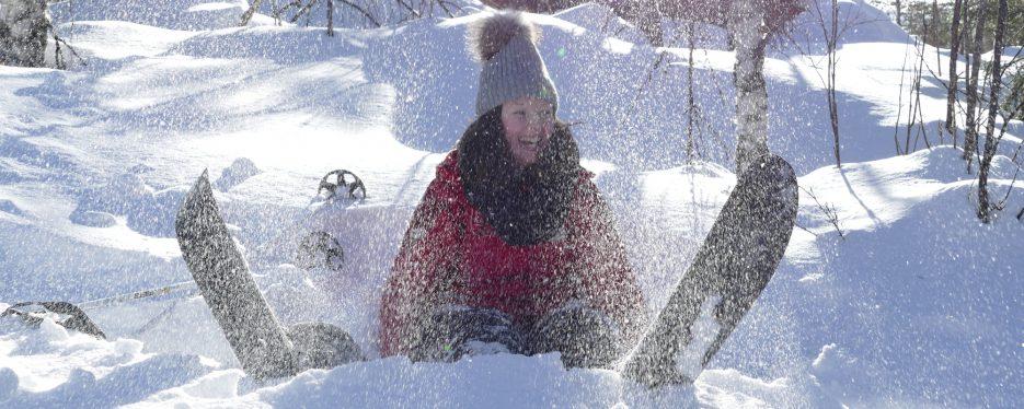Tyttö pölisyttää lunta