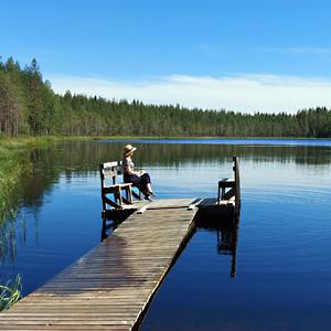 Järvi, laituri jolla nainen istuu ja taustalla metsää.