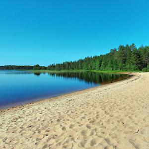 Hiekkaranta, järvi, taustalla metsää.