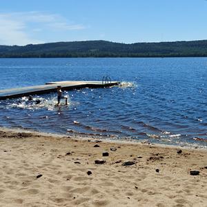 Järvi, hiekkaranta, laituri ja uimareita polskimassa järvessä.