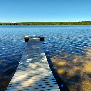 Järvi, laituri, järven takana metsää.